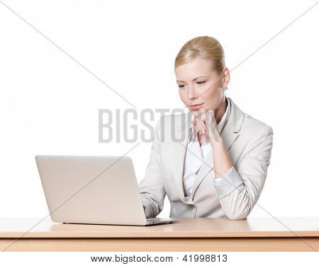 Young business woman sitting at a table with laptop, isolated