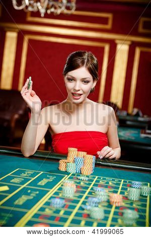 Girl gambles at the casino. Addiction to the playing roulette