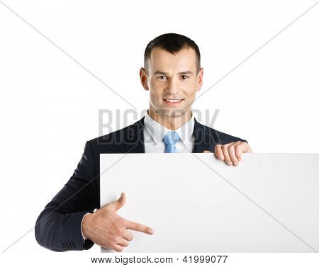 Business man points with hand at paper copyspace, isolated on white