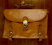Old Battered, Leather  Briefcase On Wood Background