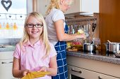 stock photo of lasagna  - Mother and daughter cooking together - JPG