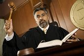 stock photo of courtroom  - Portrait of judge pounding mallet in courtroom - JPG