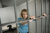 pic of jail  - Upset businesswoman standing behind bars in jail - JPG