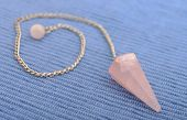 stock photo of rose-quartz  - New age rose quartz crystal pendulum on blue - JPG
