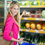 stock photo of department store  - Beautiful young woman shopping for fruits and vegetables in produce department of a grocery store - JPG
