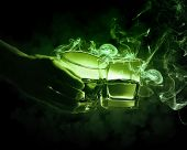 foto of absinthe  - Hand holding one of two glasses of green absinth with fume going out - JPG
