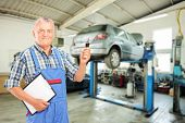 stock photo of dungarees  - Auto mechanic holding a car key at auto repair shop during an automobile maintenance service - JPG