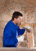 Masonry mason stonecutter man with hammer working on stone wall construction