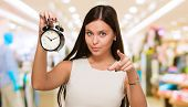 stock photo of mall  - Young Woman Holding Clock And Pointing at a mall - JPG