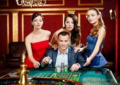 stock photo of roulette table  - Man surrounded by girls plays roulette at the casino - JPG