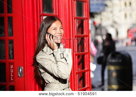 London business woman on smart phone by red phone booth. Communication concept with young multiracial Asian businesswoman on smartphone or mobile phone in London, England, United Kingdom.