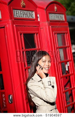 Woman taking on smartphone by London red phone booth. Young casual female business woman having conversation on mobile smart phone in London, England, United Kingdom. Multiracial Asian Caucasian model