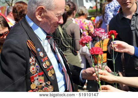 MOSCOW - MAY 9: People give flowers to veteran near Bolshoi theater, May 9, 2013, Moscow, Russia.  Every year on square in front of Bolshoi Theater traditionally gather veterans of Great Patriotic War