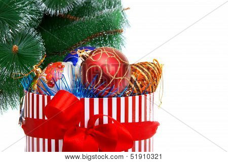 Box With Christmas Ornaments Against Fir-tree