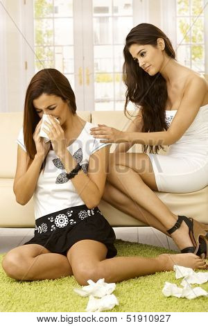 Young woman sitting on carpet crying, friend consoling her.