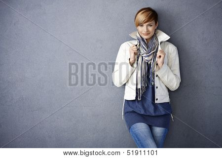 Attractive young woman in white jacket and scarf standing by grey wall