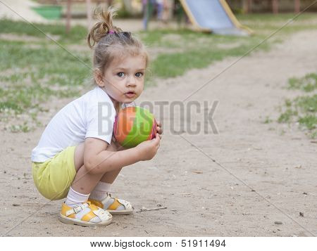 Little girl sitting on his haunches with a ball on the Playground