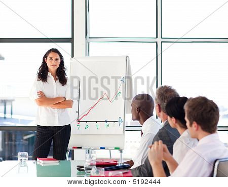 Confident Businesswoman In A Presentation With Folded Arms