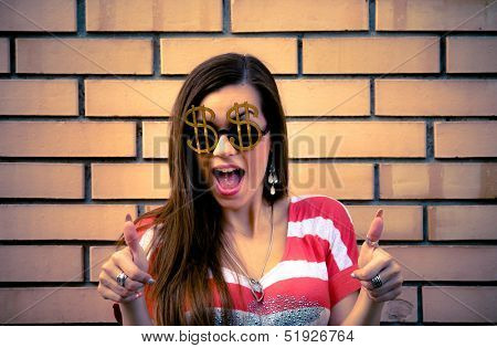 Young brunette with Dollar sign sunglasses, showing thumbs up with both hands - yellow brick wall in the background