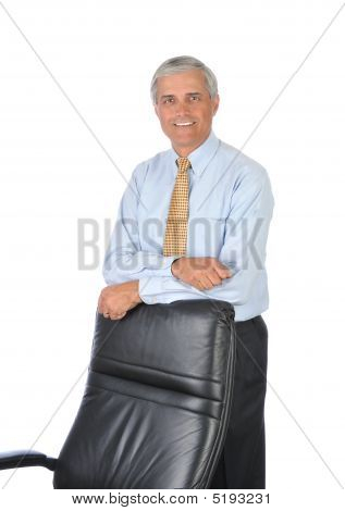 Middle Aged Businessman Leaning On Back Of His Chair