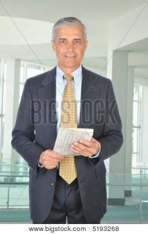 Standing Middle Aged Businessman With Financial Section