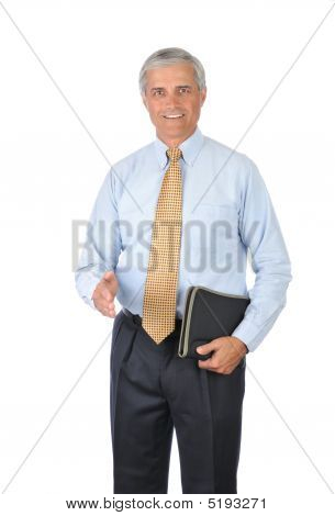 Middle Aged Businessman With Notebook And Hand Extended To Shake