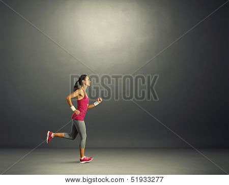 young beautiful sportswoman running in the dark room