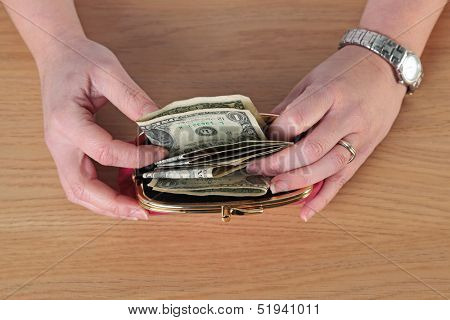Overhead close up photo of a woman taking money out of her purse.