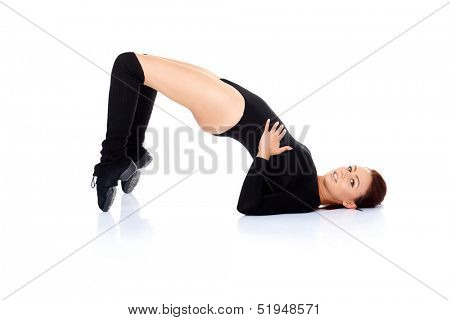 Attractive young woman doing fitness exercises in a black leotard balancing on the tips of her toes and shoulders to strengthen and tones her muscles  on white