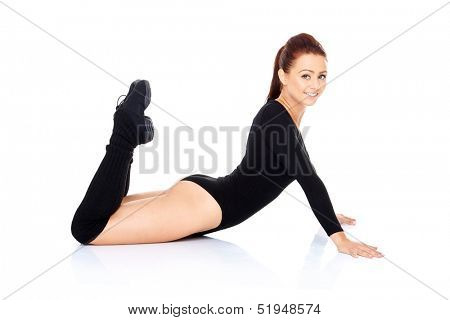 Fit sporty woman exercising and working out strengthening her abdominal muscles doing press ups and leg raisers over a white background