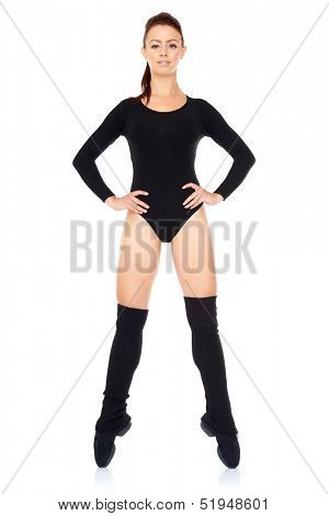 Confident athletic young woman working out in a leotard standing en pointe balanced on the tips of her toes with her hands on her hips isolated on white