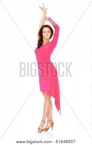 Vivacious beautiful woman dancing in a sexy pink dress balancing on one foot in her high heels with her arms outspread  on white