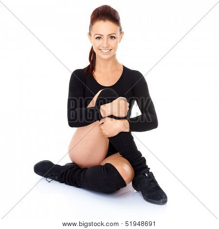 Smiling friendly supple woman with a beautiful smile sitting on the floor with her legs and arms intertwined during training exercises to maintain her fitness and increase mobility  on white