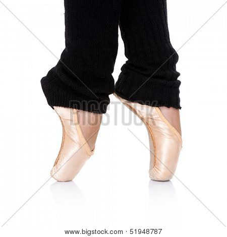 Ballet dancer posing en pointe on the tips of her toes as she practices her ballet  over a white background