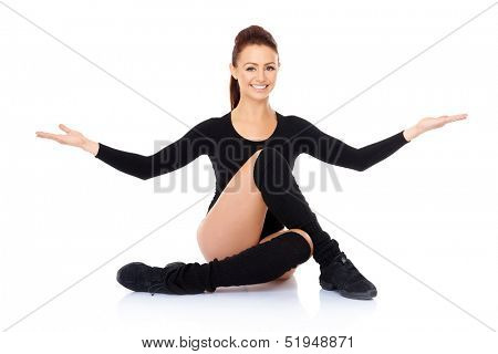 Smiling friendly supple woman with a beautiful smile sitting on the floor with her legs intertwined during training exercises to maintain her fitness and increase mobility  on white