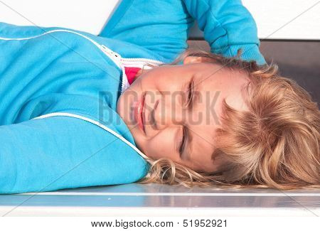Little Blond Girl In Casual Sport Outwear Lies And Relaxes With Smile On White Park Bench