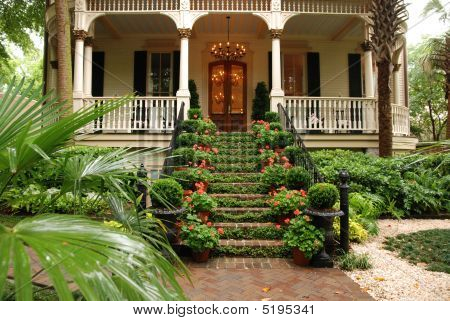 Colorful Historic Colonial Home Entrance With Flowers, Ivy And Porch