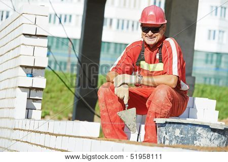 Portrait of Builder construction mason worker bricklayer with trowel putty knife outdoors