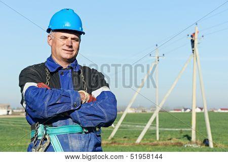 Portrait of power line repairman electrician worker on electric post pole work