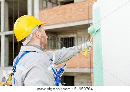 builder worker painting facade of high-rise building with roller