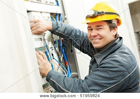 One electrician builder at work installing energy saving meter into electric line distribution fuseboard