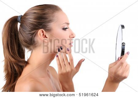 Beautiful girl preens before small mirror isolated on white