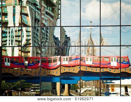 Docklands Light Railway train reflected on a building