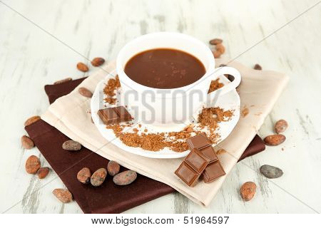 Cocoa powder in cup on napkin on wooden table