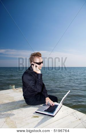 Using Phone And Laptop On The Pier