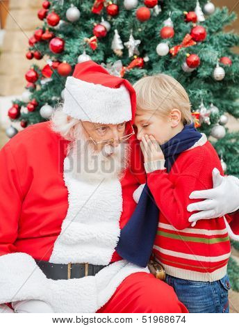Boy telling wish in Santa Claus's ear in front of Christmas tree