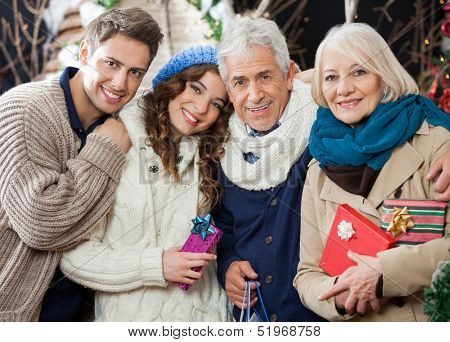 Portrait of happy loving family with Christmas presents and shopping bags standing in store
