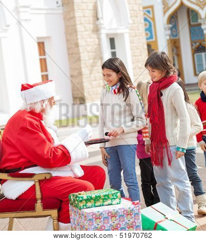 Children standing in a queue to take biscuits from Santa Claus against house