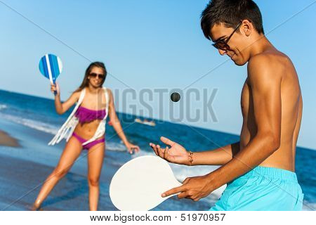 Teen Couple Playing Smash Ball Beach Tennis.