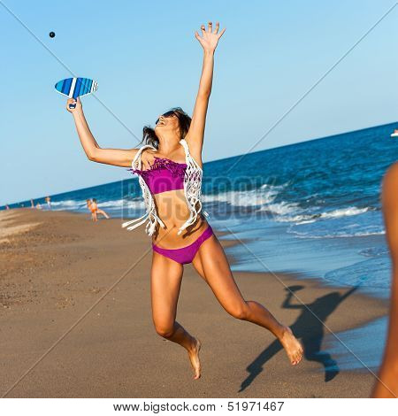 Teen Girl Jumping At Ball On Beach.